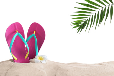 Pink flip flops and plumeria flower on sand against white background, space for text. Beach objects