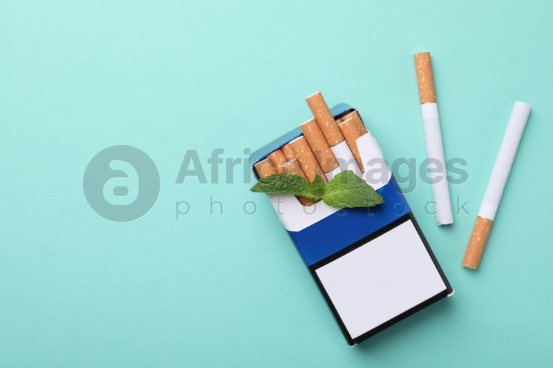 Pack of menthol cigarettes and mint on turquoise background, flat lay. Space for text
