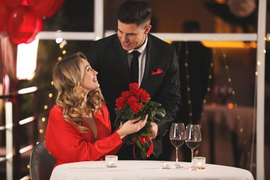 Man presenting roses to his beloved woman in restaurant at Valentine's day dinner