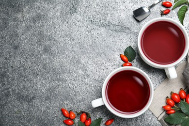 Fresh rose hip tea and berries on grey table, flat lay. Space for text