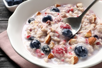 Tasty oatmeal porridge with toppings on wooden table, closeup