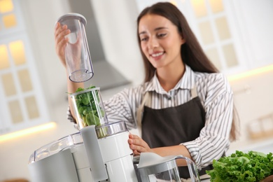 Young woman making tasty fresh juice in kitchen, focus on hands