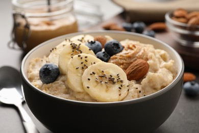 Tasty oatmeal porridge with toppings served in bowl on table, closeup