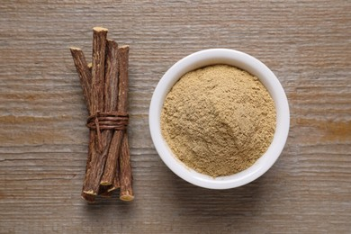 Powder in bowl and dried sticks of liquorice root on wooden table, flat lay
