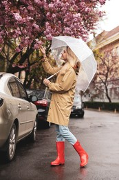 Young woman with umbrella near blossoming tree on spring day