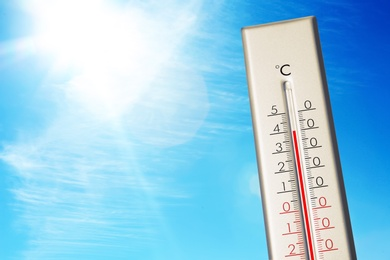 Weather thermometer showing high temperature and blue sky on background