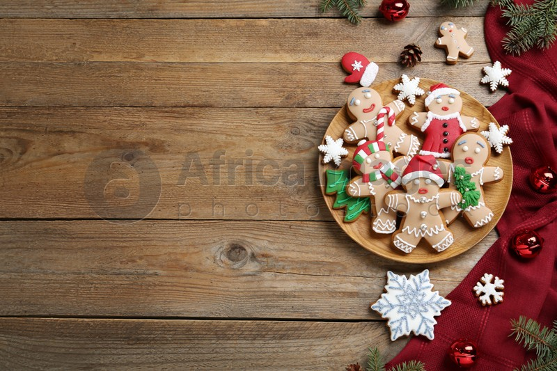 Delicious Christmas cookies and festive decor on wooden table, flat lay. Space for text