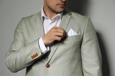 Man fixing handkerchief in breast pocket of his suit on grey background, closeup