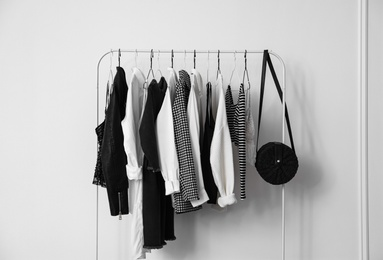 Rack with stylish clothes near white wall