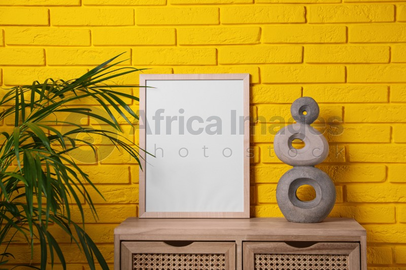 Empty frame and decor on wooden cabinet near yellow brick wall. Mockup for design