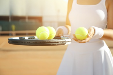 Sportswoman with racket and tennis balls at court, closeup