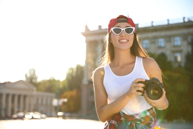 Young photographer with professional camera outdoors. Space for text