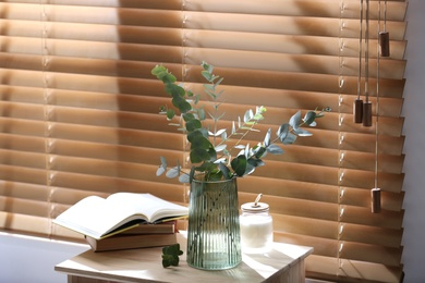 Vase with fresh eucalyptus branches on table near window in room. Interior design