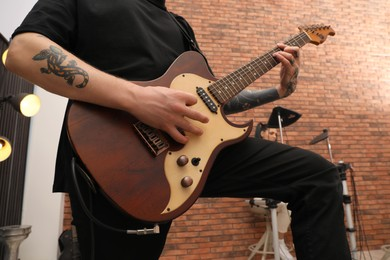 Man playing electric guitar during rehearsal in studio, closeup. Music band practice