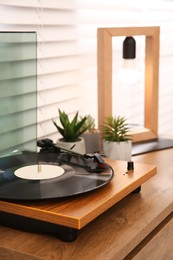Stylish turntable with vinyl record on wooden chest of drawers indoors