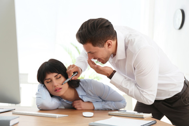 Man drawing on colleague's face while she sleeping at workplace. April fool's day