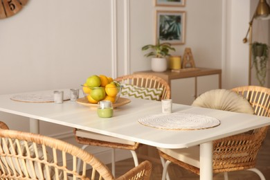 Stylish white dining table and wicker chairs in room. Interior design