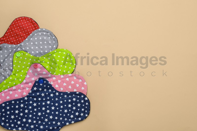 Many reusable cloth menstrual pads on beige background, flat lay. Space for text