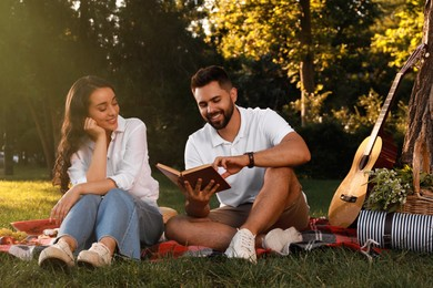 Happy young couple reading book on plaid in park. Summer picnic