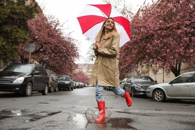 Young woman with umbrella walking on spring day
