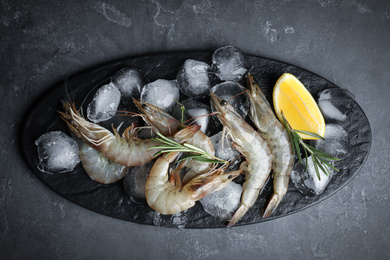 Raw shrimps with lemon slices and rosemary on grey table, top view