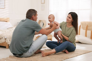 Happy family with their cute baby on floor in bedroom