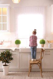 Little girl washing dishes in kitchen at home, back view