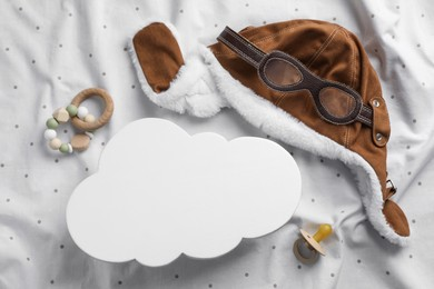 Flat lay composition with cloud shaped child's night lamp on white fabric