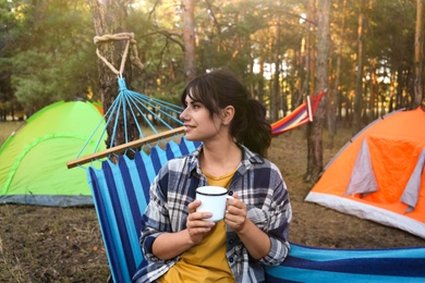 Woman with drink resting in comfortable hammock outdoors
