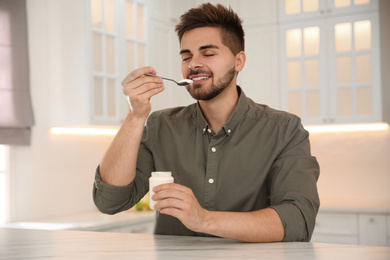Happy young man eating tasty yogurt at table in kitchen