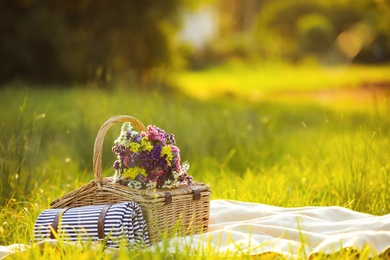 Picnic basket with wildflowers and mat on blanket outdoors. Space for text