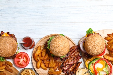 Flat lay composition with fresh bacon burgers and fries on white wooden table. Space for text