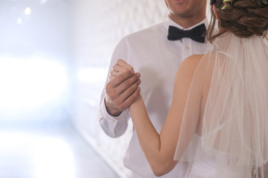 Happy newlywed couple dancing together in festive hall, closeup