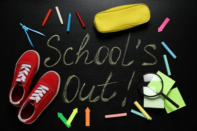 Shoes, stationery and text SCHOOL'S OUT written on blackboard, flat lay. Summer holidays