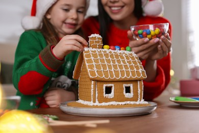 Mother and daughter decorating gingerbread house at table indoors, closeup