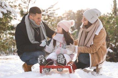 Happy family with sledge outdoors on winter day. Christmas vacation