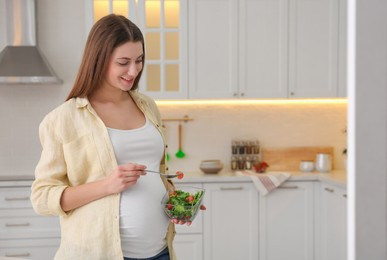 Young pregnant woman with vegetable salad in kitchen, space for text. Healthy eating