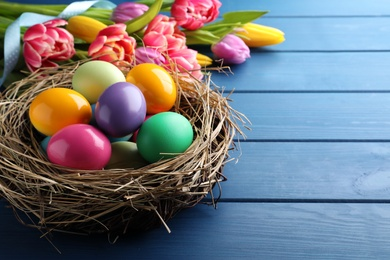 Bright painted eggs and spring tulips on blue wooden table, closeup view with space for text. Happy Easter