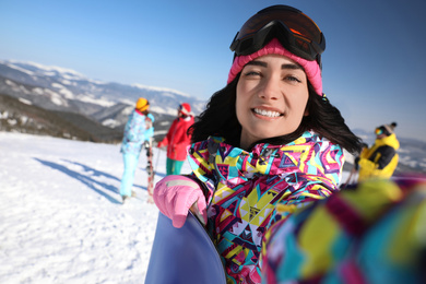 Young woman with snowboard taking selfie at ski resort. Winter vacation