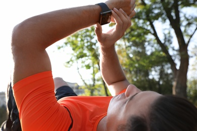 Man checking fitness tracker during training outdoors, closeup