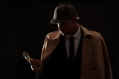 Old fashioned detective with magnifying glass on dark background
