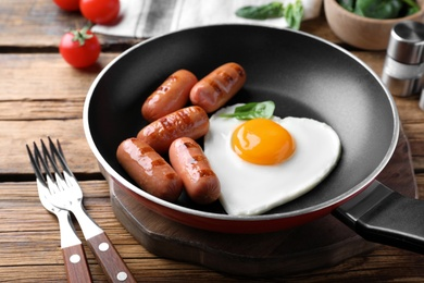 Romantic breakfast with fried sausages and heart shaped egg on wooden table. Valentine's day celebration