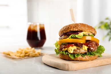 Board with tasty burger on table. Space for text