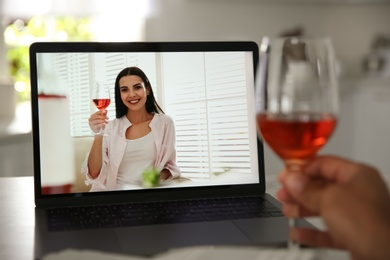 Friends drinking wine while communicating through online video conference in kitchen. Social distancing during coronavirus pandemic