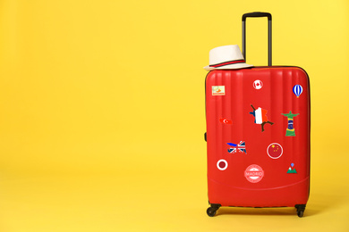 Red suitcase with travel stickers on yellow background. Space for text