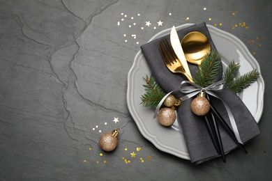 Festive table setting with beautiful dishware and Christmas decor on black background, flat lay. Space for text
