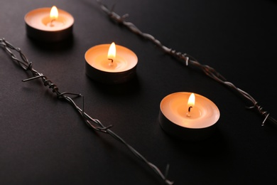 Burning candles and barbed wire on black background. Holocaust memory day