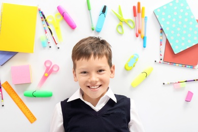 Cute child surrounded by school stationery on white background