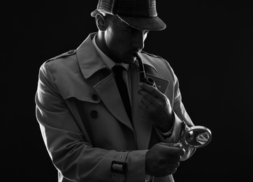 Old fashioned detective with magnifying glass smoking pipe on dark background, black and white effect