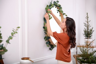 Woman decorating mirror with eucalyptus branches at home. Space for text